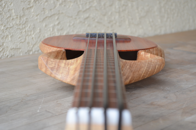 "The Chtukulele uses dual ""Jet Intake"" soundholes. These ports are carved into the upper bout. With this design we don't have to cut a hole in the soundboard which allows us to lighten up the bracing. Plus it looks wicked cool, right?"