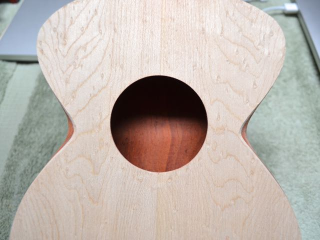This is a beautiful detail at the waist. Viewed from the front, the waist curves slightly in so you can see slender little darts of color on either side of the sound hole.